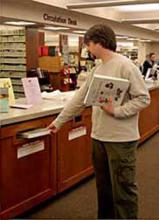 Man returning materials into the book drop at the Circulation Desk.