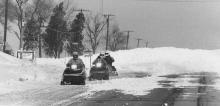 Snowmobilers Kirk Kresis, Wilbur Clark, and Tim Woods make their way down U.S. 45 near Curtis Road south of Champaign.